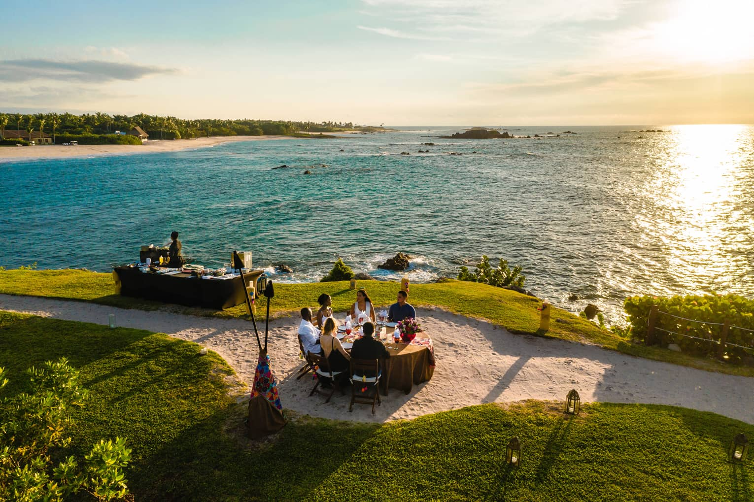 Aerial view of Dinner on the Rock dining table on lawn, sandy path near ocean at sunset