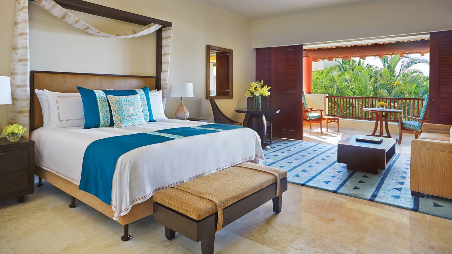 Garden-View Casita bed with blue-and-yellow Mexican print pillows, living room, sliding wood doors to patio