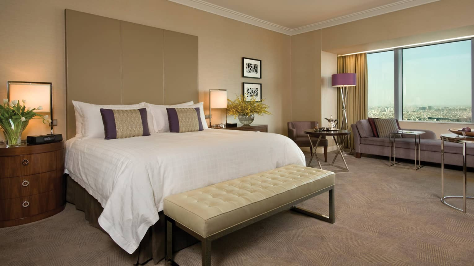 Deluxe hotel room bed with tall padded headboard and leather bench, beige carpet, long chaise at window