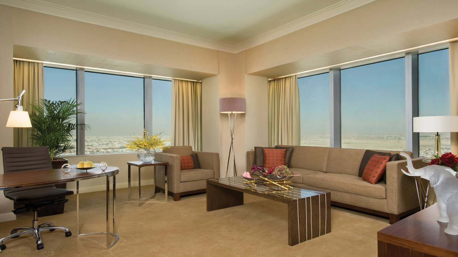 Large corner suite living room with sunny windows and city views, beige sofa and armchair, long wood coffee table
