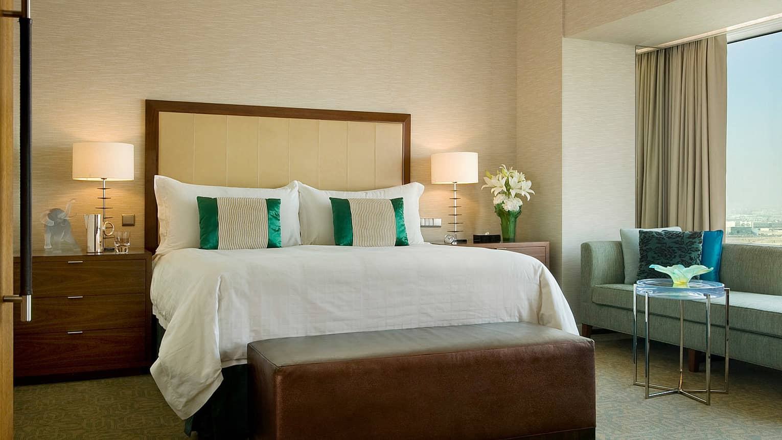 Hotel room bed with green-and-white silk accent pillows, brown leather bench at foot, green sofa at window