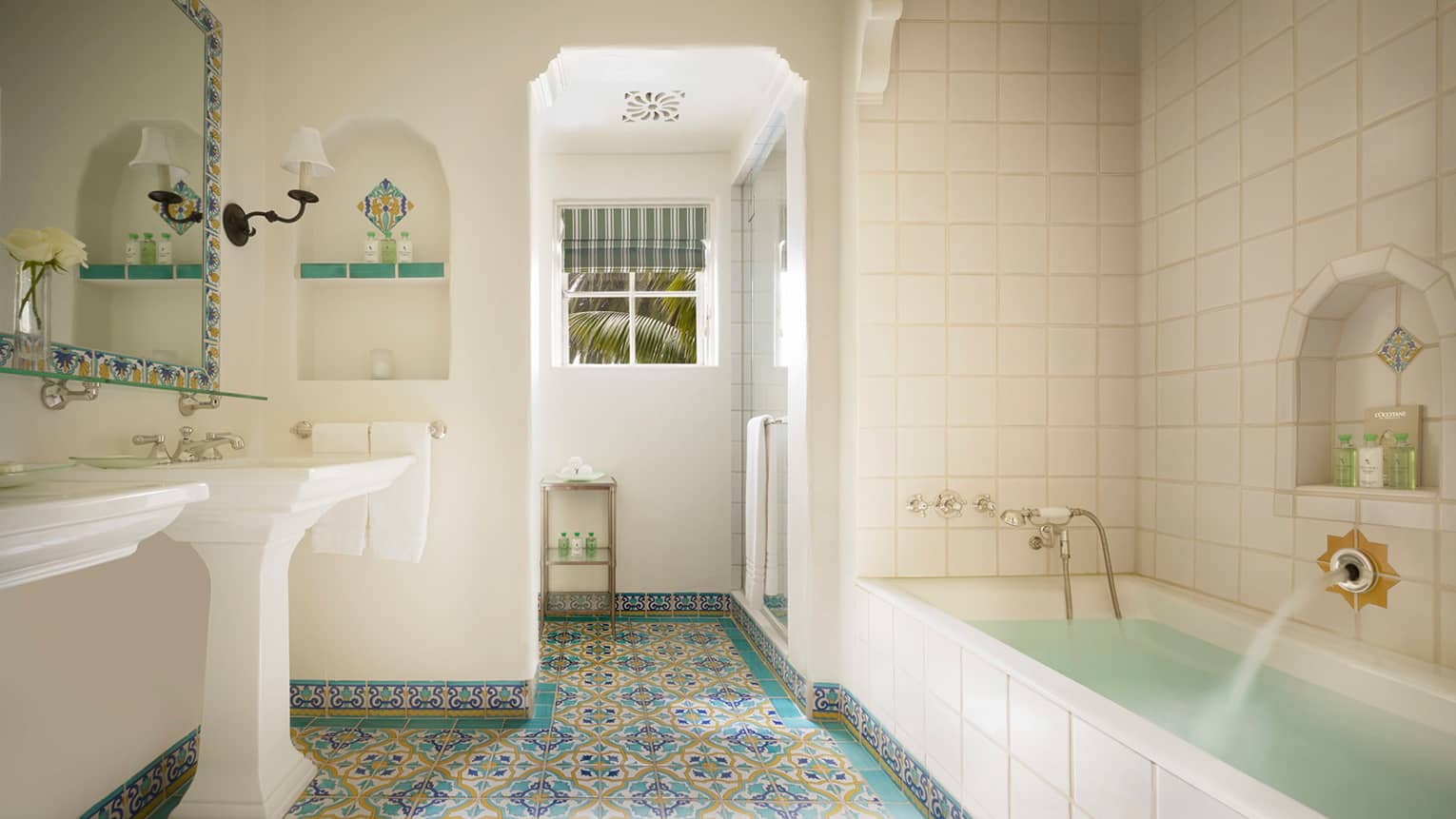 White tile bathroom, long tub, colourful Spanish Colonial-style tiles