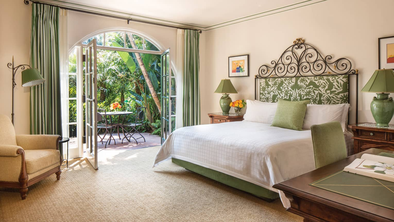 Open double French doors to patio, table by bed with iron headboard, green accents