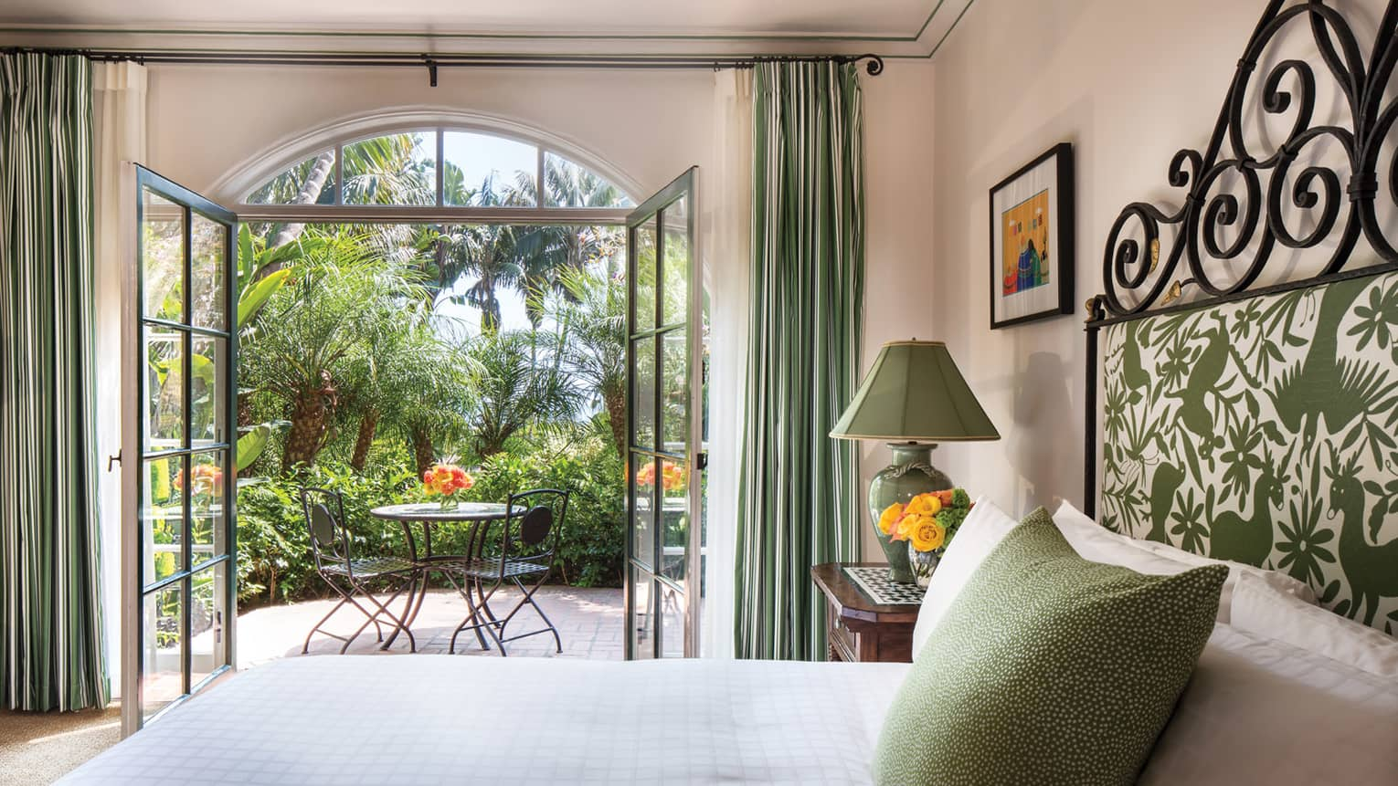 Garden Room open glass doors to sunny balcony, green lamp, pillow, headboard over bed