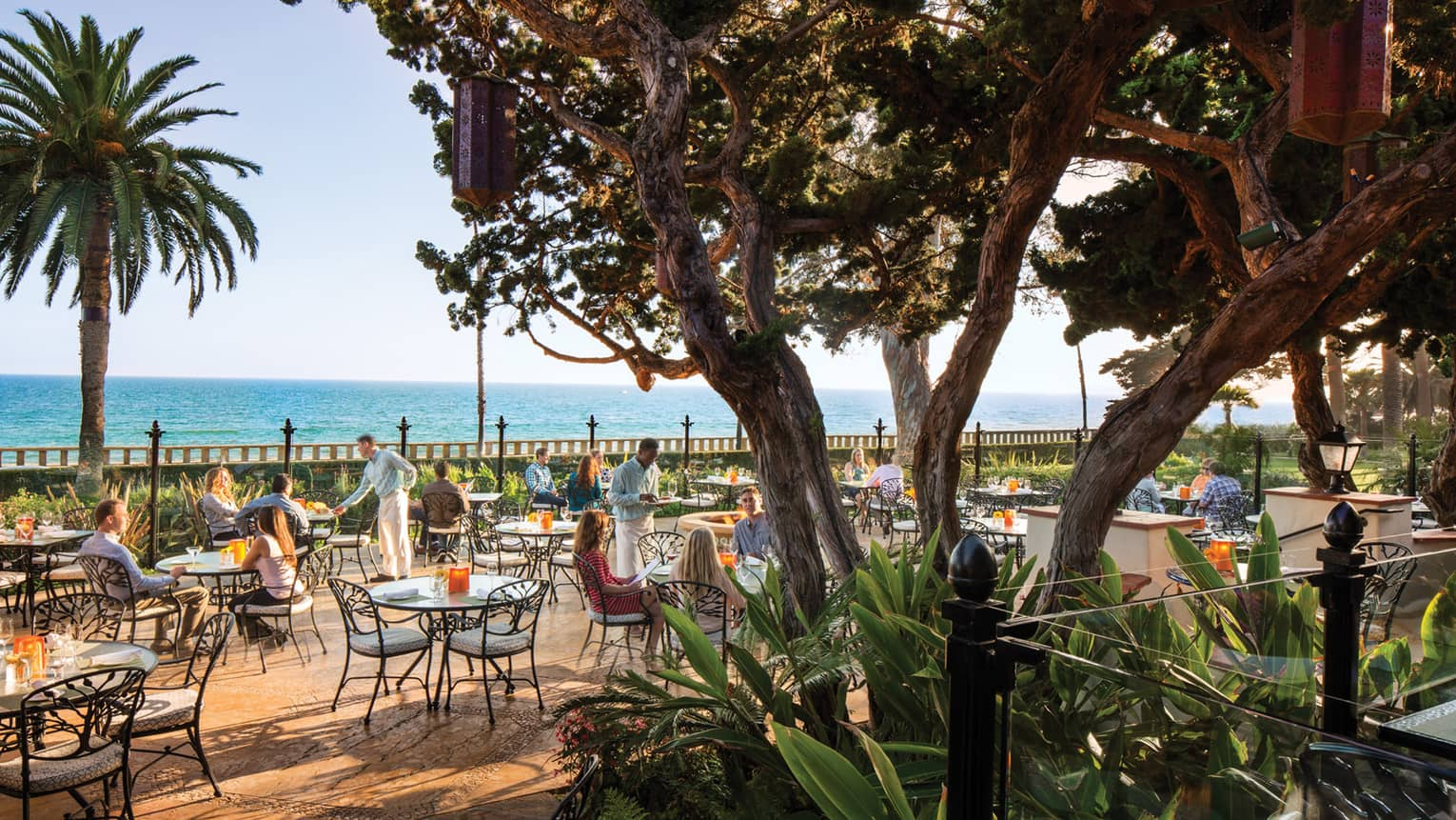 View of diners on Bella Vista patio at wrought-iron tables, chairs through large trees, plants