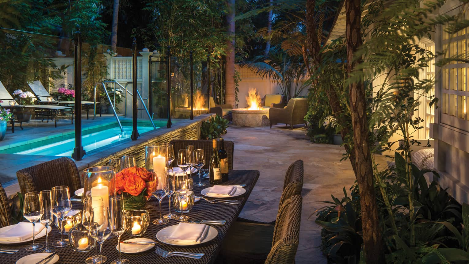 Ty Warner bungalow backyard candle-lit patio dining table by plunge pool, fire pit at night