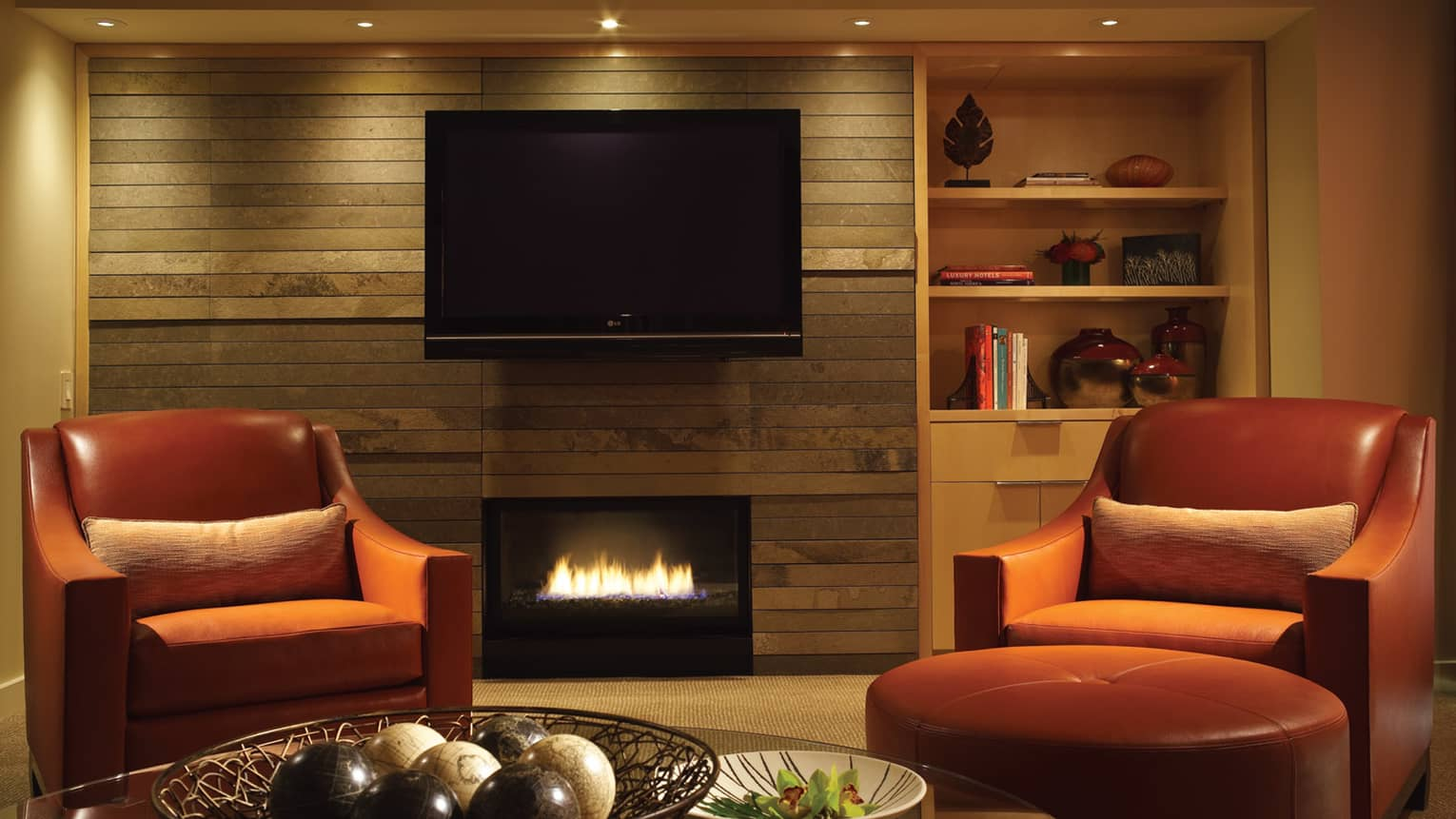Red armchair beside gas fireplace, TV mounted on wall
