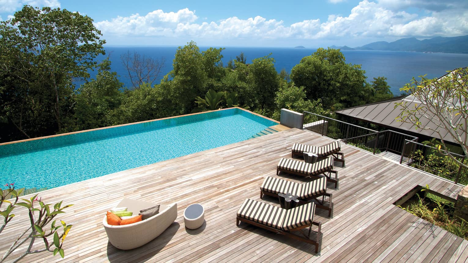 Looking over large deck with wood lounge chairs, sofa, plunge pool