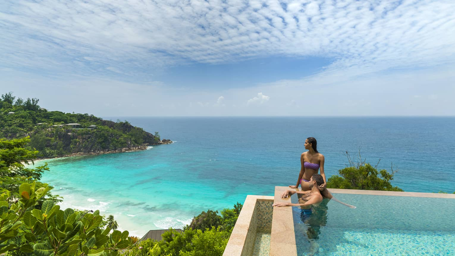 Woman and man stand at edge of infinity pool overlooking tropical mountain forest, ocean