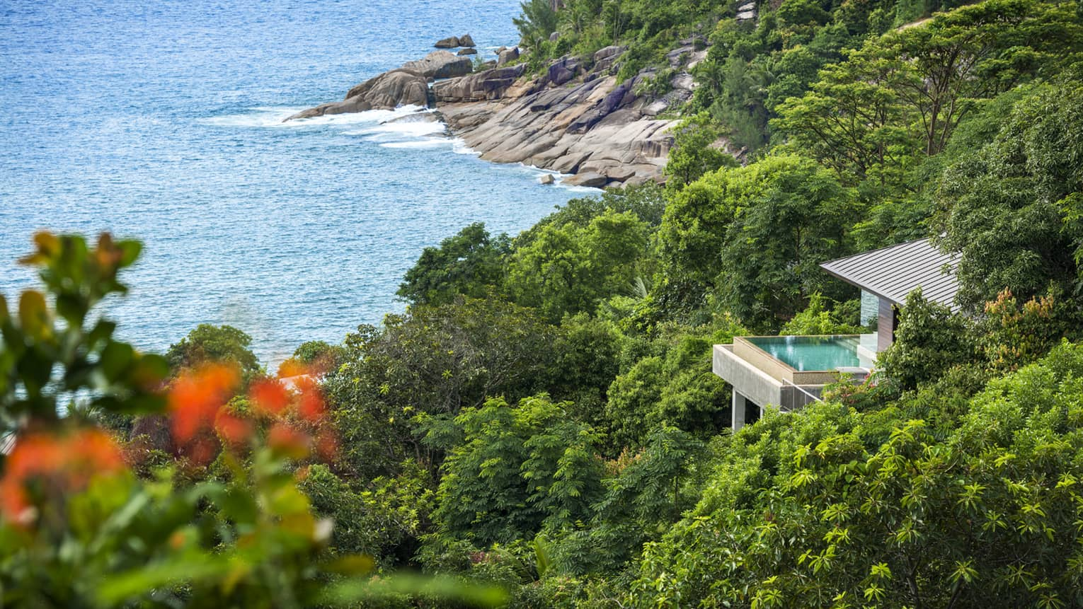 Overview of Villa nested among greenery, ocean and rocky shore below