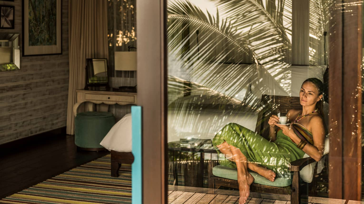 Woman relaxes on chair, drinks coffee behind glass door of Garden View Villa Bedroom