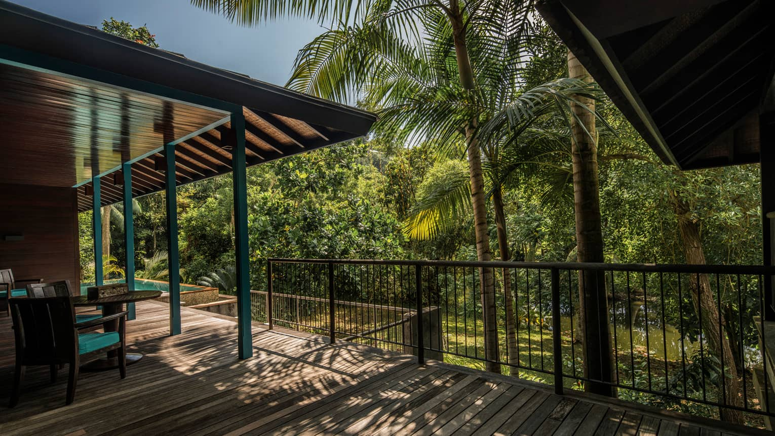 Palm trees cast shadows over Garden Villa wood deck, roof