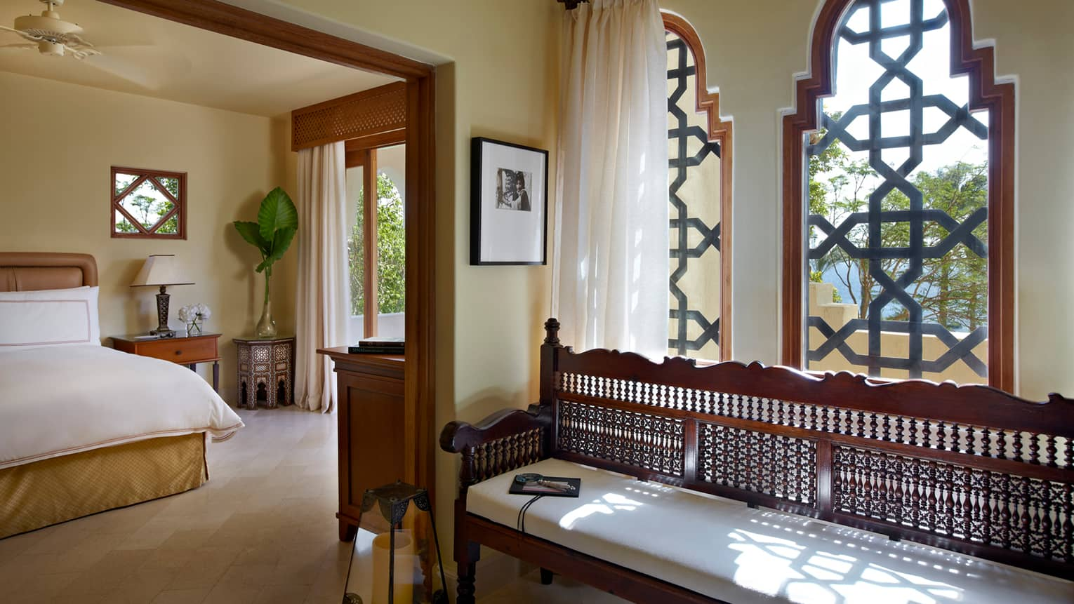 Four Bedroom Villa sunny bedroom with bed, nightstand, balcony door, long decorative wood bench with white cushion