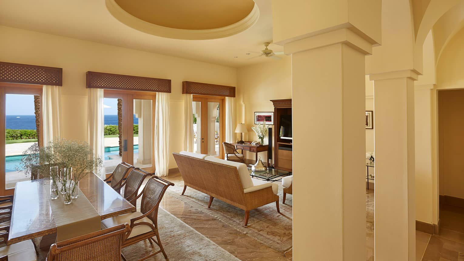 Presidential Suite dining area, living room under white recessed ceiling, pillars, large balcony doors to pool