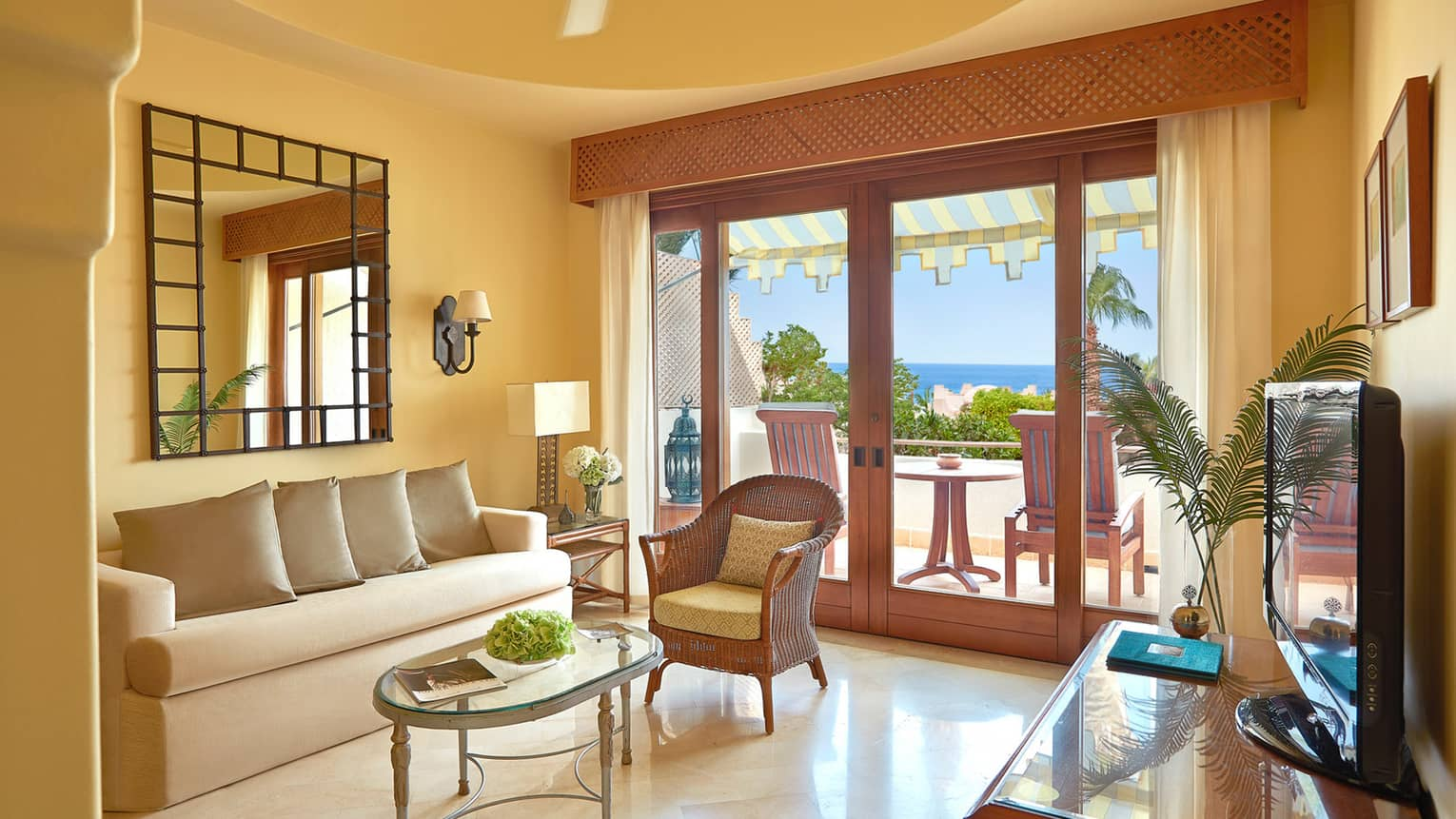 Two-Bedroom Sea-View Family Suite sofa, wicker armchair , TV, doors to sunny balcony