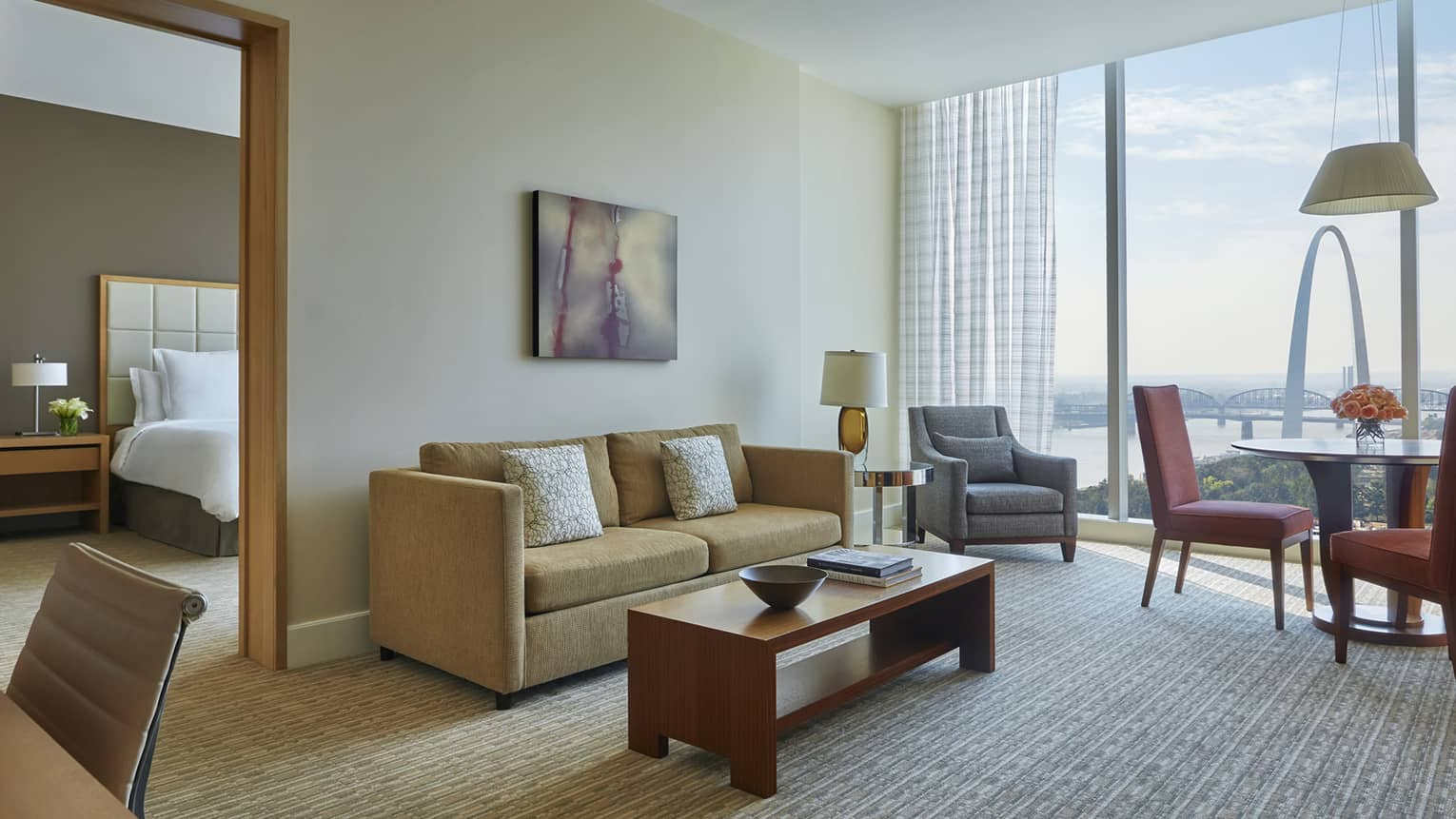 Arch one-bedroom suite living room with gold sofa, grey armchair and dining table, near separate bedroom