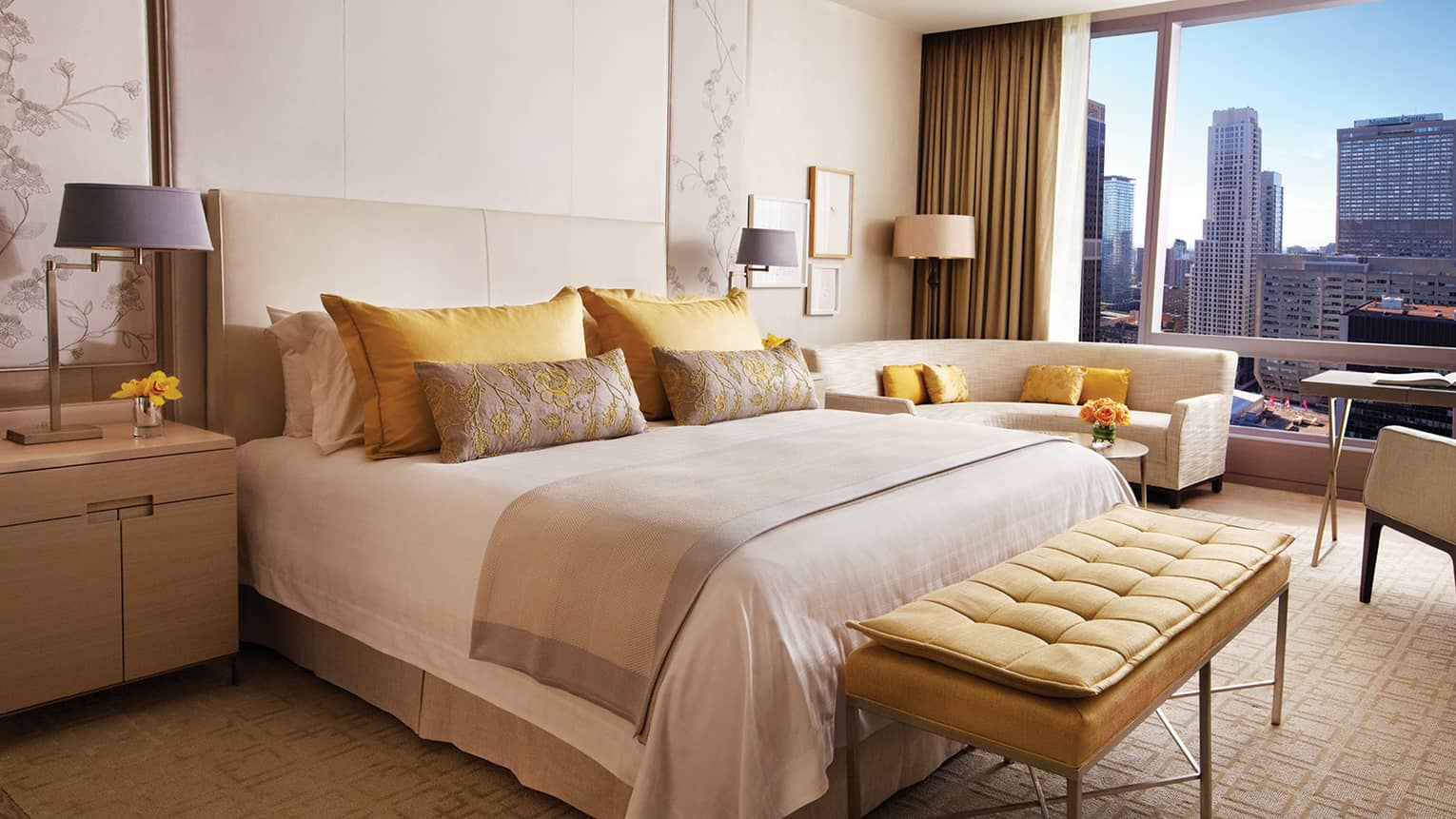 Plush yellow bench at foot of bed with yellow, gold pillows by curved loveseat, window