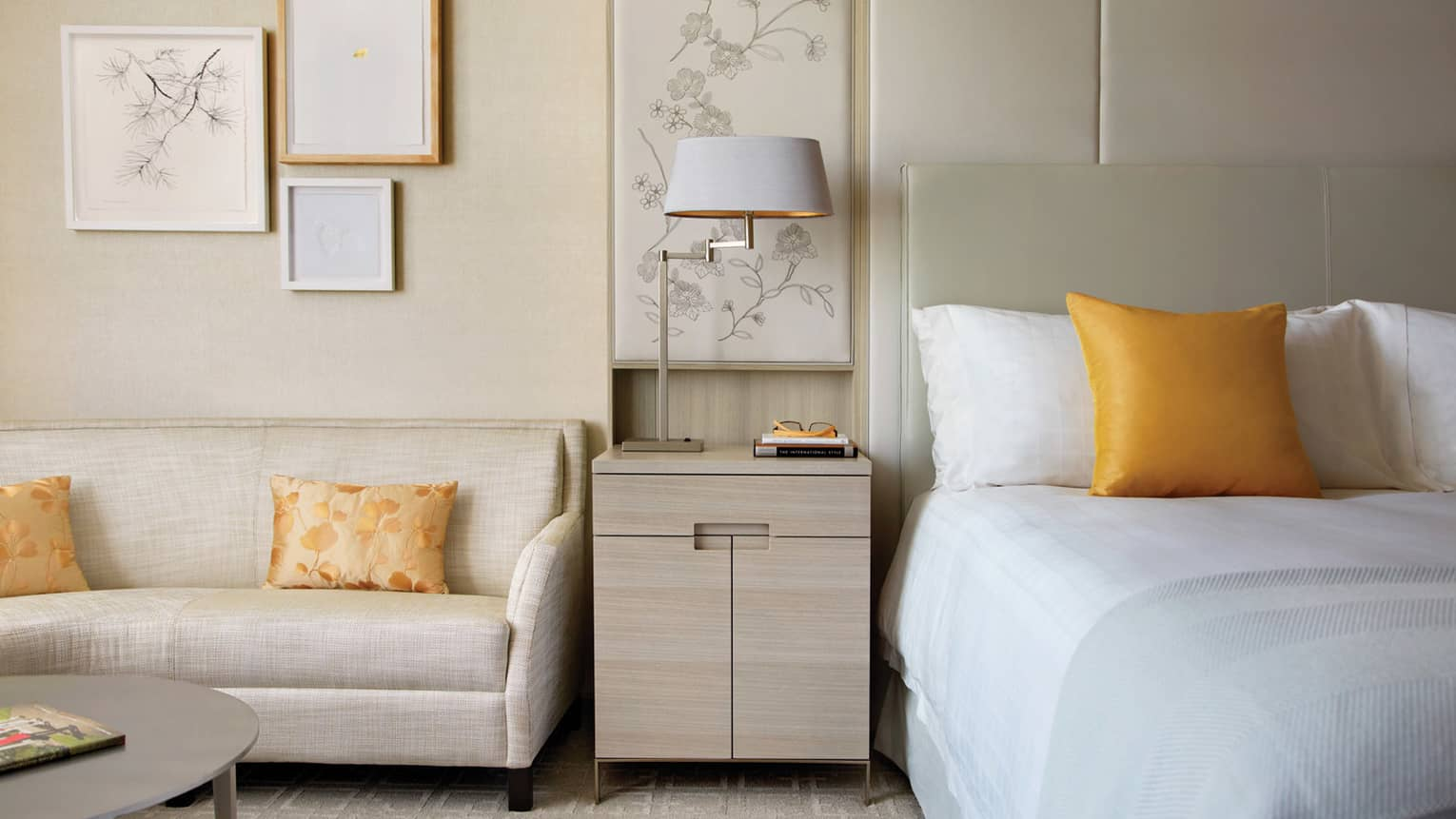 White loveseat by light wood nightstand, bed with golden yellow accent pillow