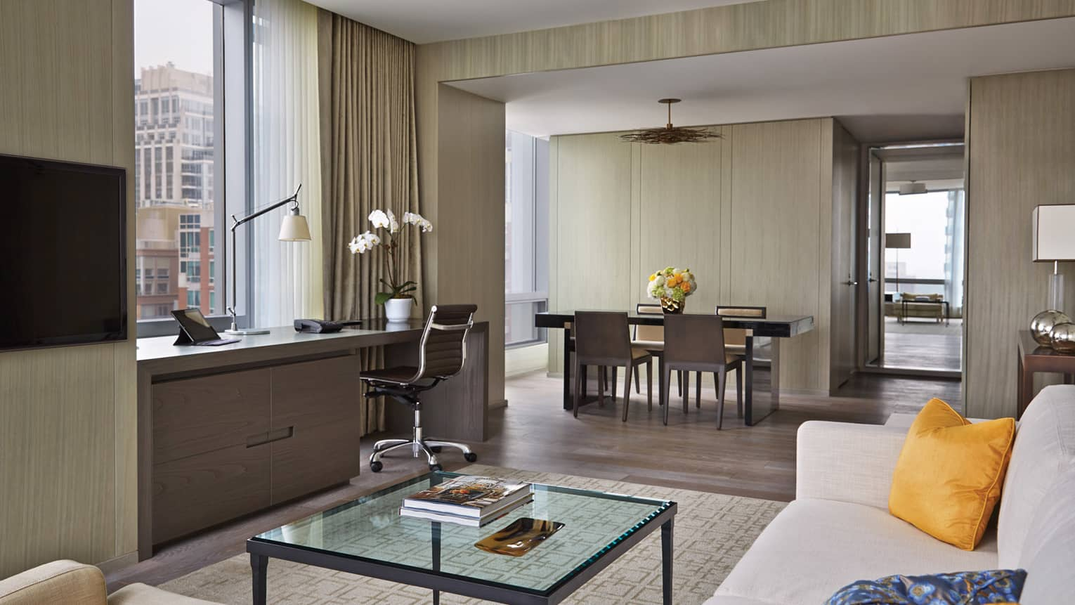 Yorkville Suite living room, glass table, desk under window, dining room by bedroom door