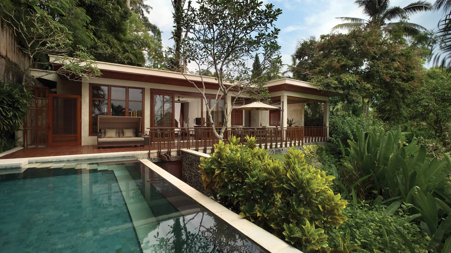 Exterior of Sayan Villa looking past pool and garden, up at deck and white bungalow with wood trim