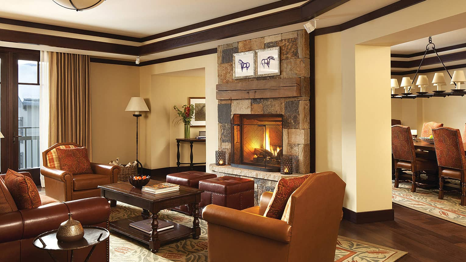 Brown leather sofa and armchairs in front of brick fireplace and fire, ranch-style dining table in view