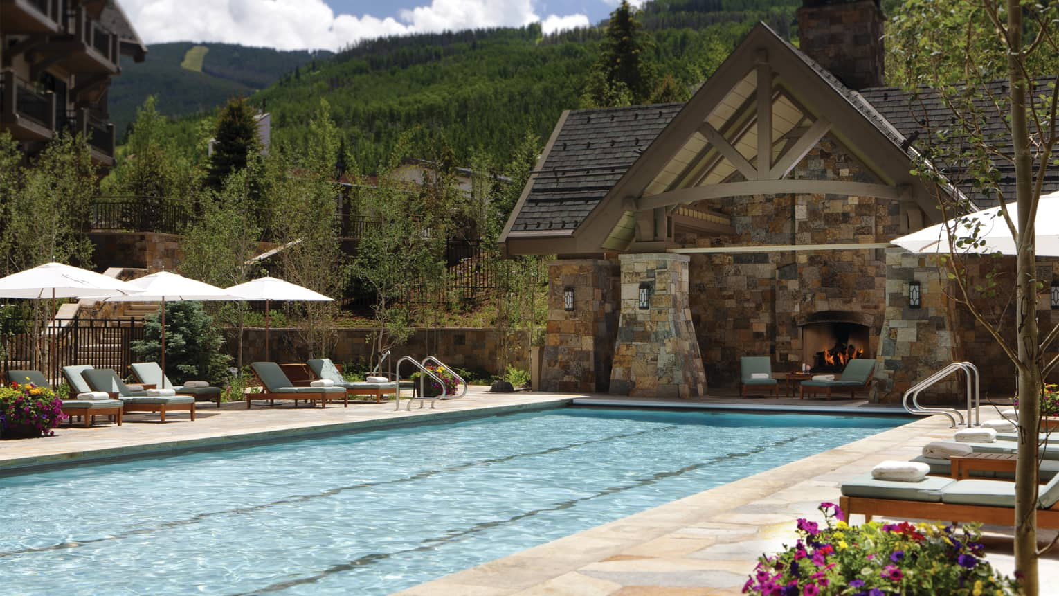 Year-round outdoor pool with brick patio and chalet-style cabana with fireplace and lounge chairs