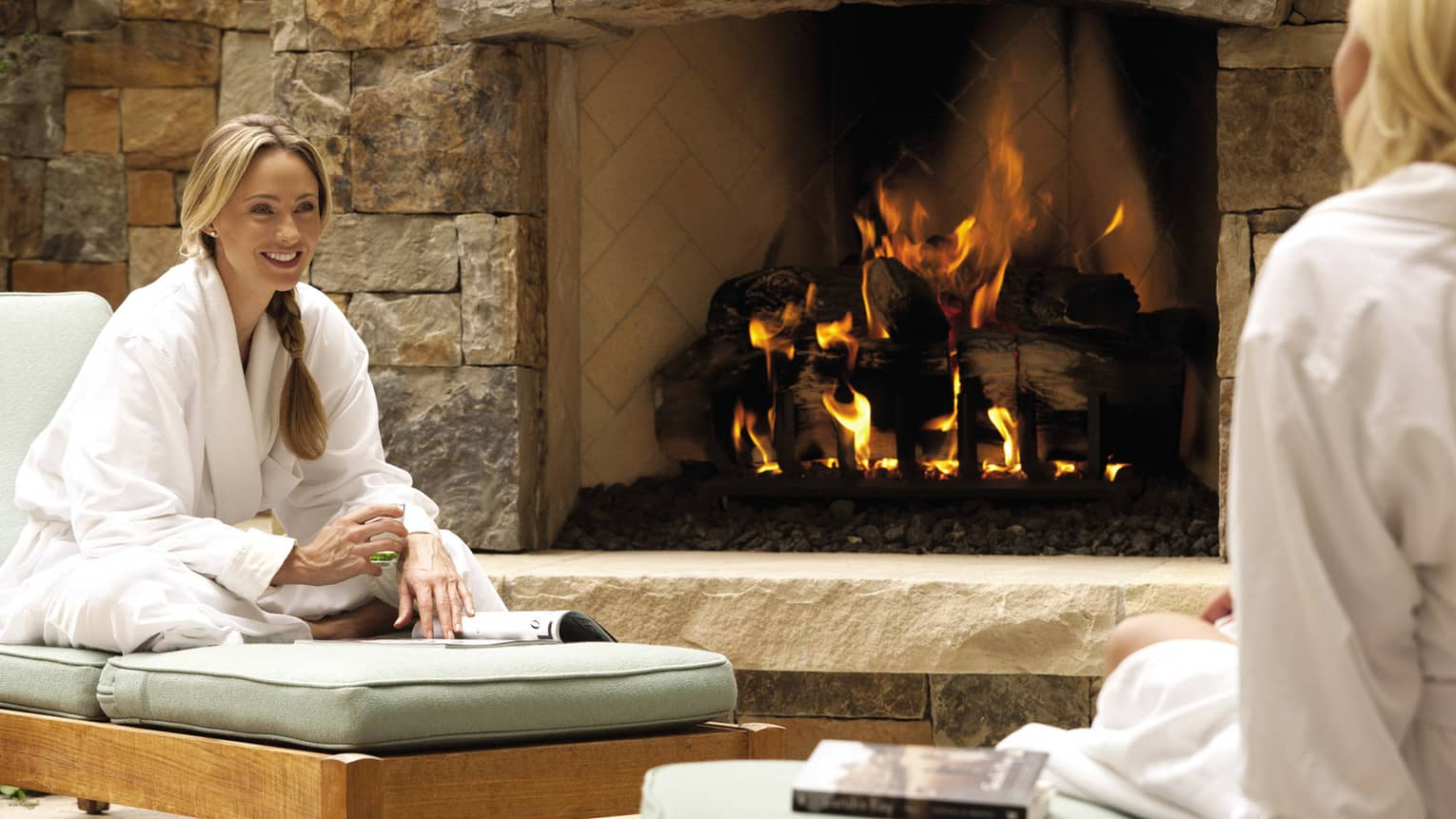 Two women lounge in spa robes by a fireplace.