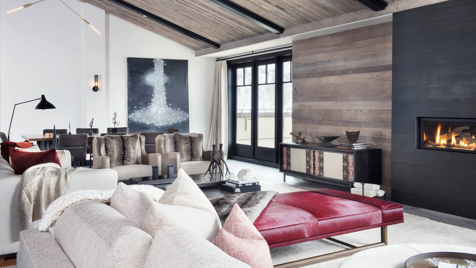 Modern four-bedroom designer residence with white decor, sloped ceilings, red leather chaise, fireplace