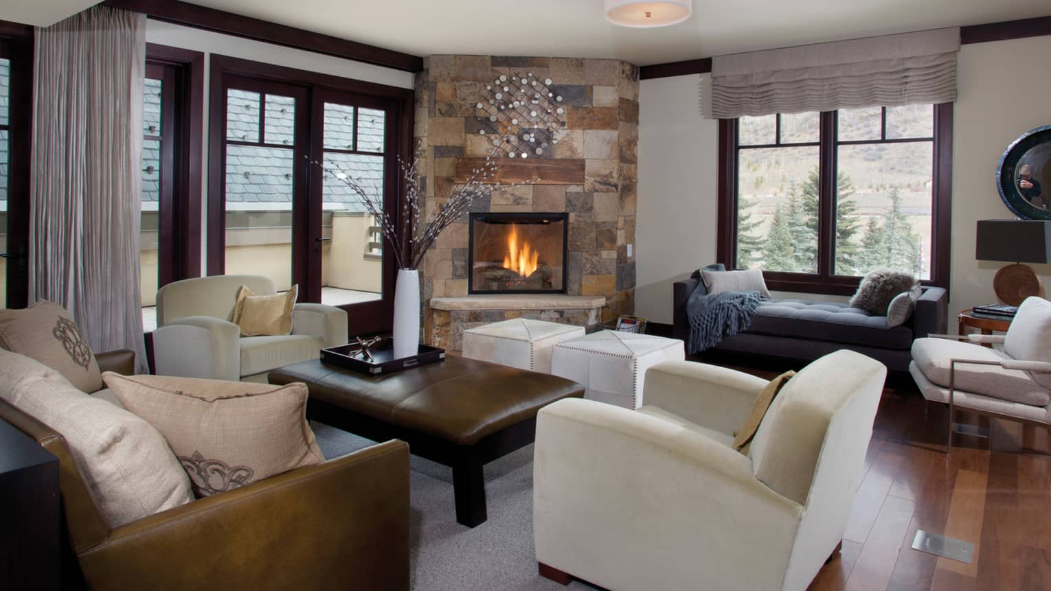 Two-bedroom residence suite living area with leather sofa and coffee table, window chaise, stone fireplace