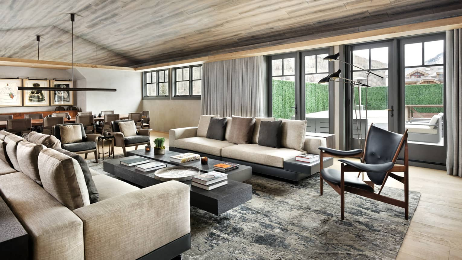 Long plush sofas, modern leather armchairs around large coffee table in bright living room