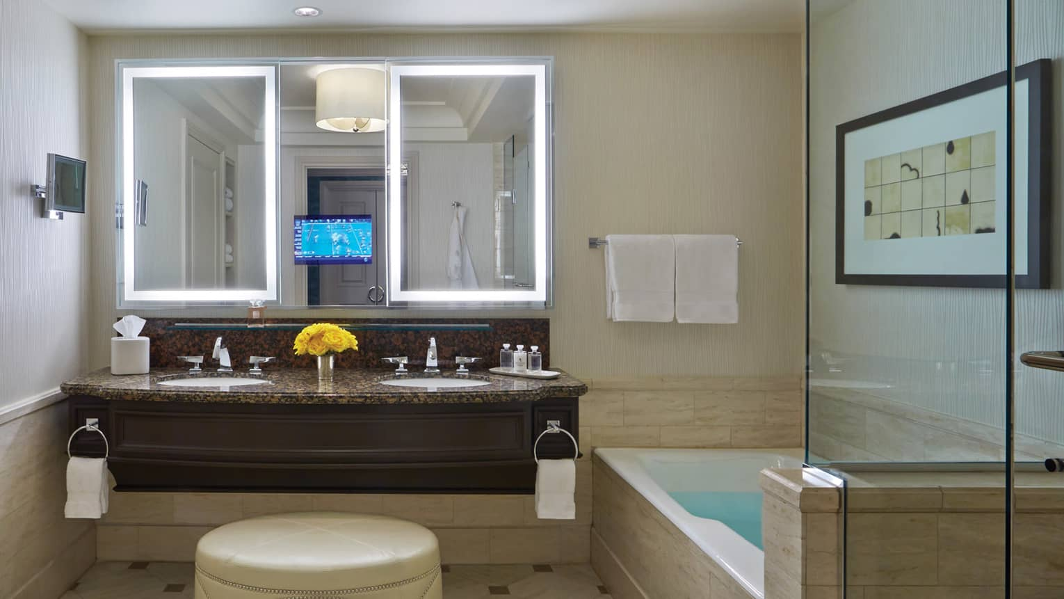 Hotel bathroom with double sink vanity, bathtub with glass wall