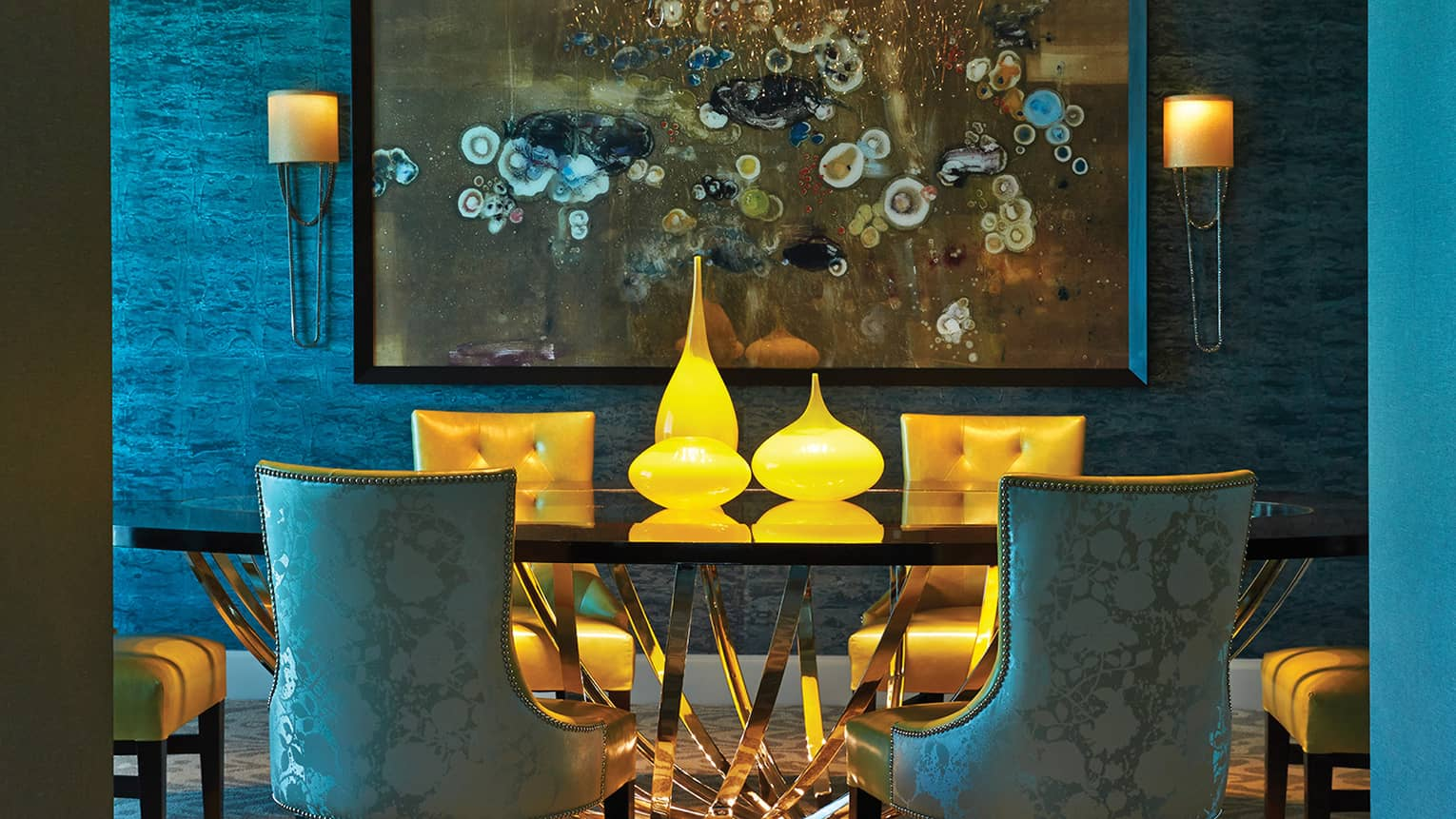 Blue silk and gold leather dining chairs under modern chain chandelier, framed painting