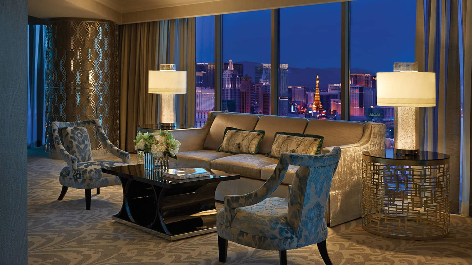 Hotel suite's living room with sofa, two chairs and two illuminated lamps, overlooking Las Vegas at night
