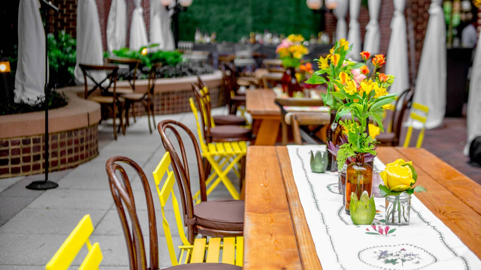 Colourful flowers, chairs, linens around outdoor patio dining tables