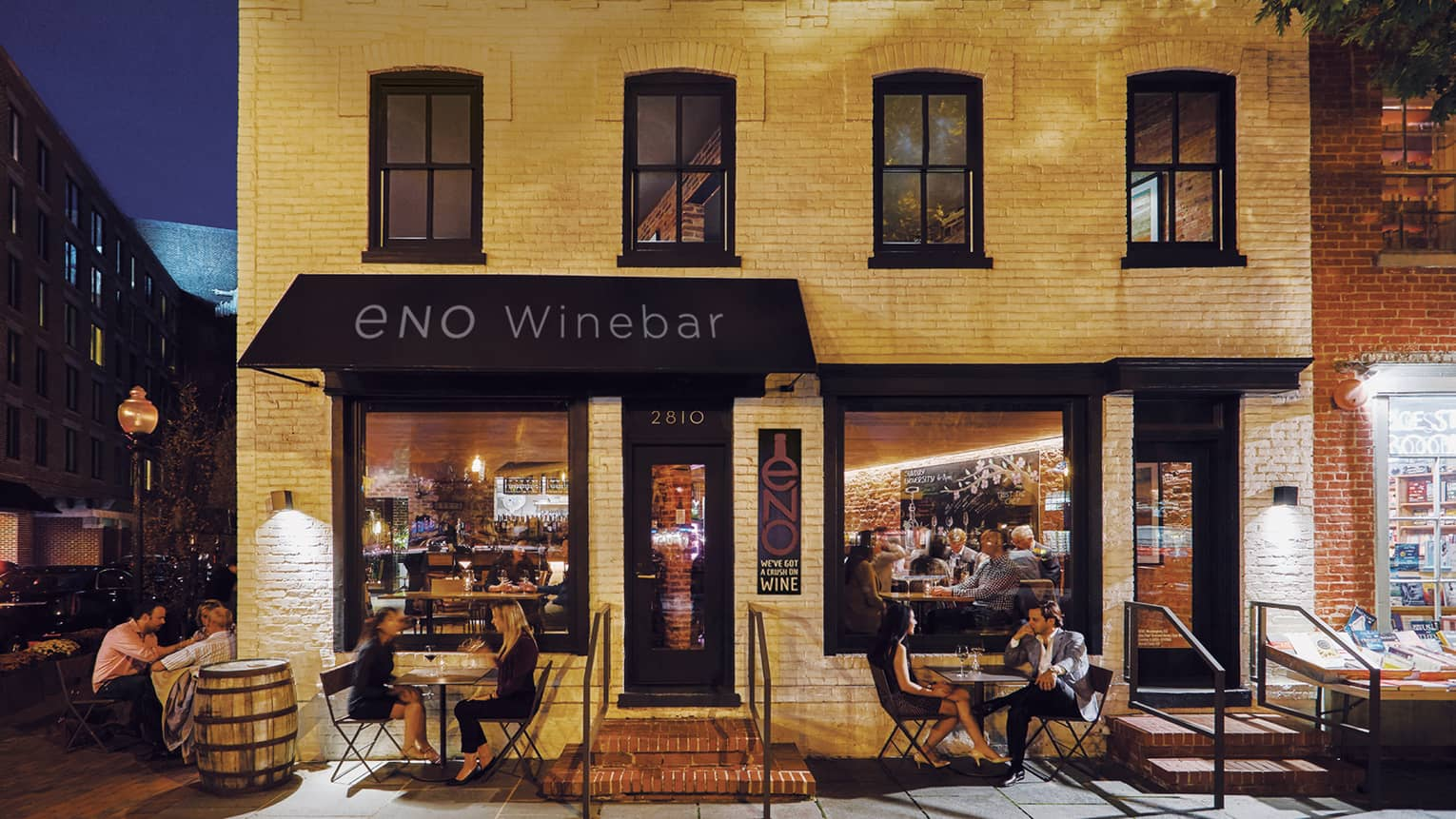 ENO Wine Bar, people dine on patio under black awning, white brick building exterior at night
