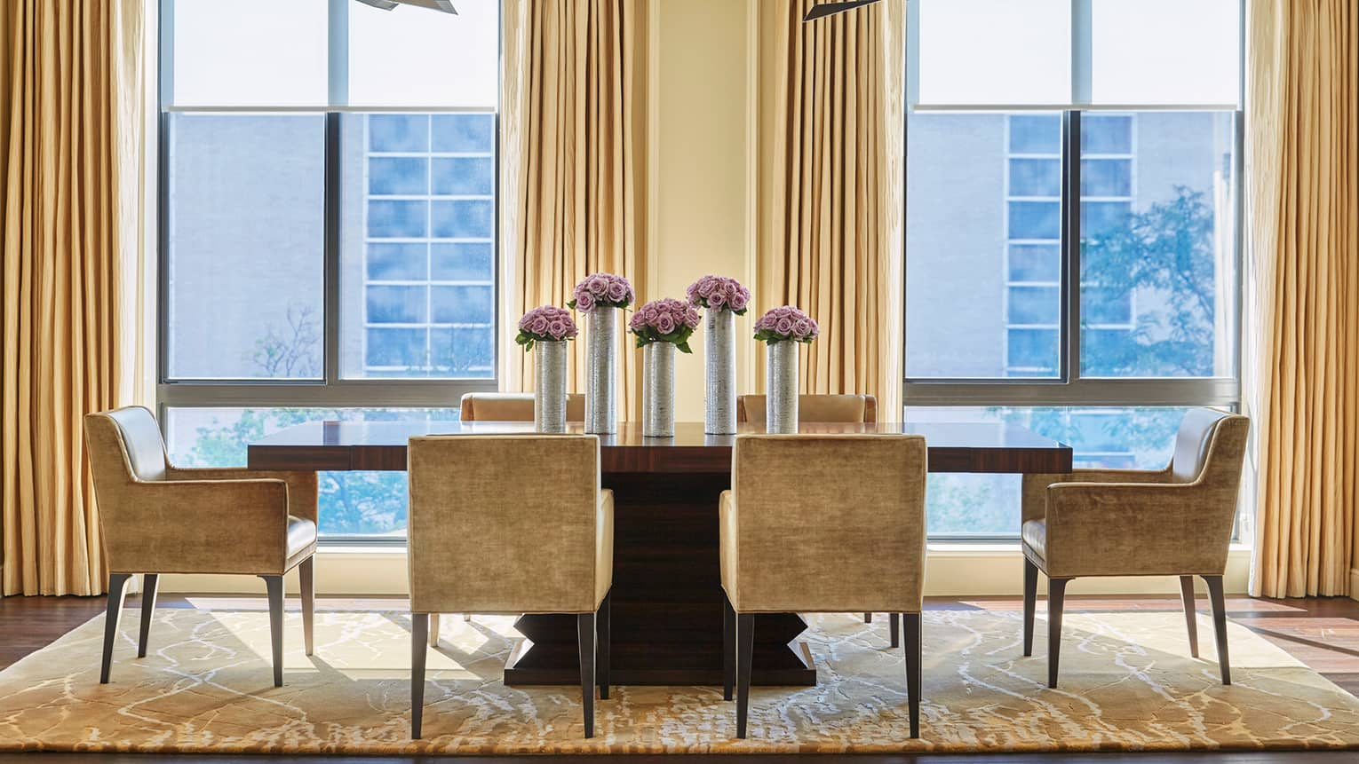Imperial Suite modern dining table with golden brown velvet dining chairs around long wood table with tall silver vases, purple flowers