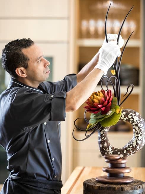 Portrait photo of Executive Pastry Chef Rabii Saber adjusting chocolate garnish