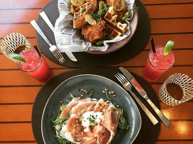 Aerial view of cured meat dish, fried chicken on waffles, pink lemonades