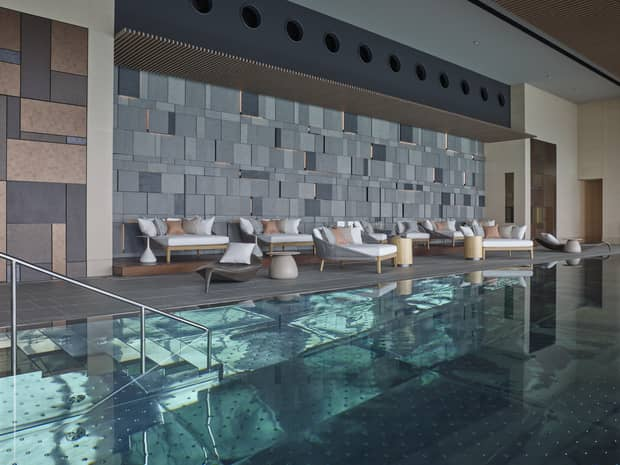 Indoor swimming pool, plush patio chairs on deck under modern brick wall