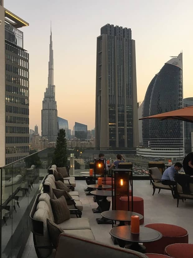 Lounge chairs along Four Seasons International Financial Centre hotel rooftop patio at sunset