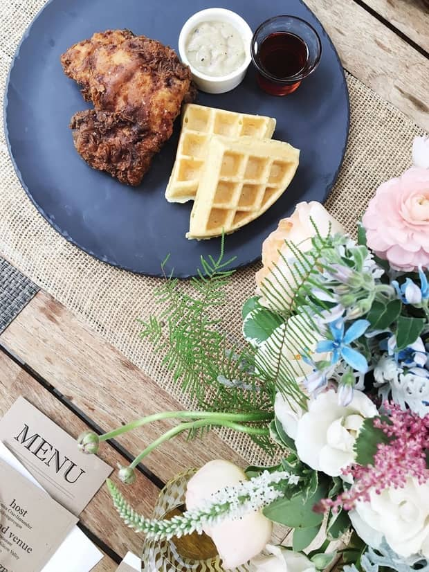 Fried chicken and waffles on plate by fresh bouquet of roses, flowers