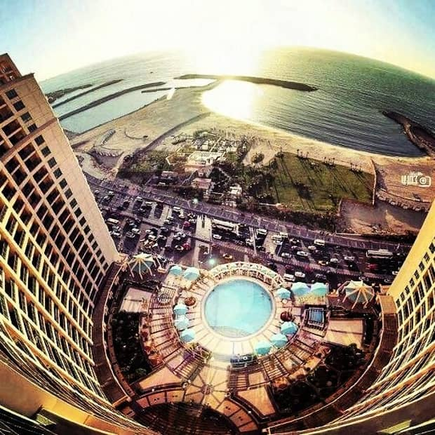 Aerial Fisheye Lens View Of Hotel Building Exterior Parking Lot Road Beach And