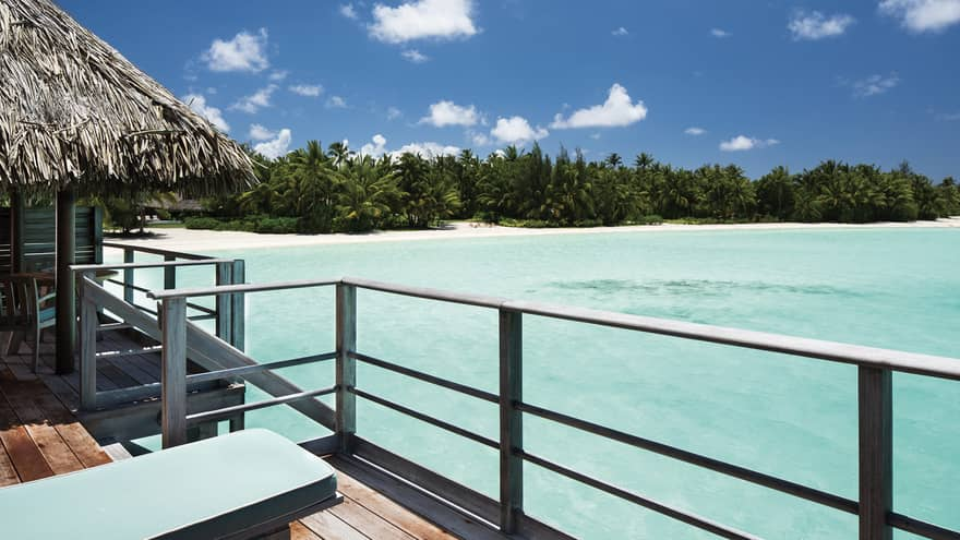 Overwater Bungalow Deck Railings Looking Out At Shallow Blue Lagoon And White Sand Beach