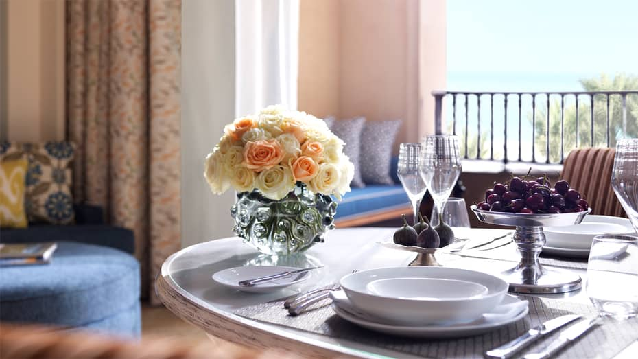 In-room dining table set with white dishes, wine glasses, fresh cherries, figs and pink roses