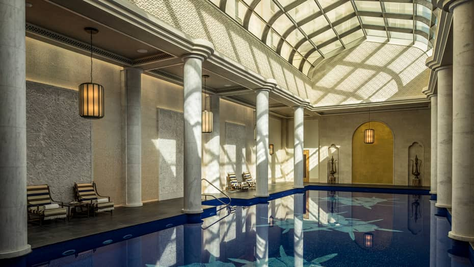Long indoor swimming pool under curved skylights and tall white pillar columns