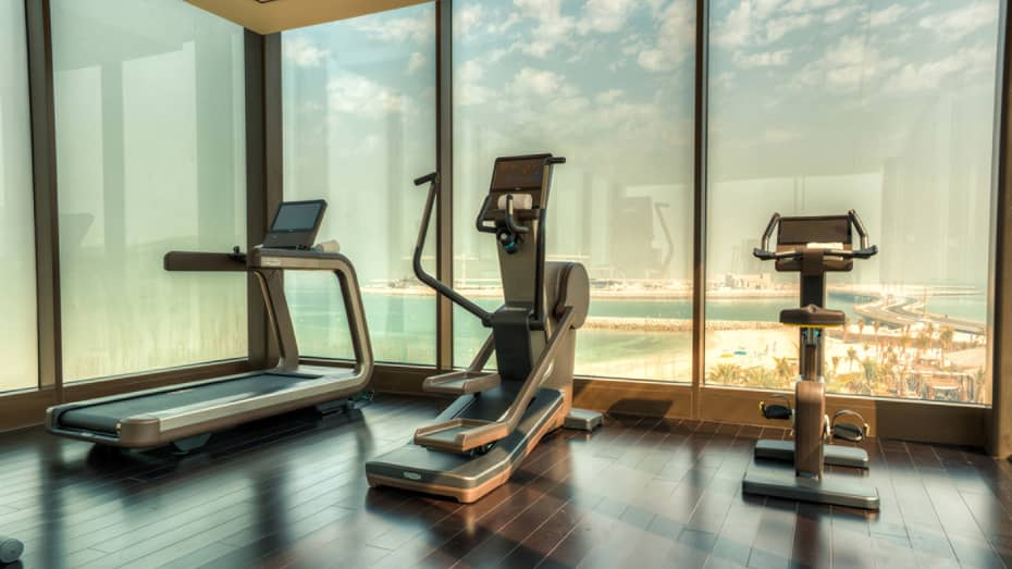 A treadmill, elliptical machine and cardio bike side-by-side at window overlooking beach
