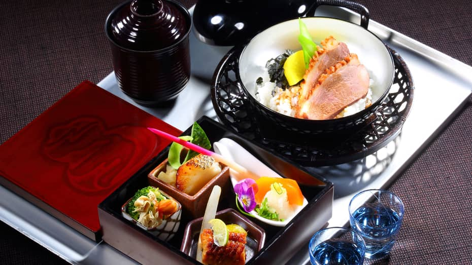 Close-up of white in-room dining tray with assortment of fish, rice and Japanese dishes in decorative bowls