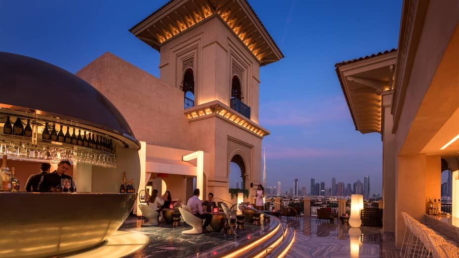 Rooftop lounge at night, with modern gold bar and guests sitting on white chairs, city skyline visible