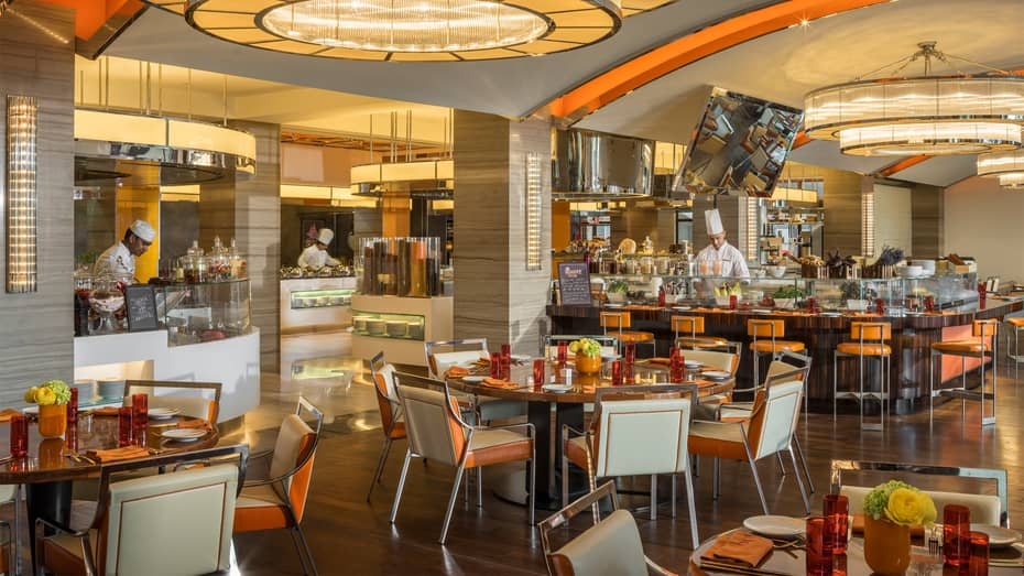 Suq market-style casual dining room with white-and-orange decor, chefs at cafeteria-style counters