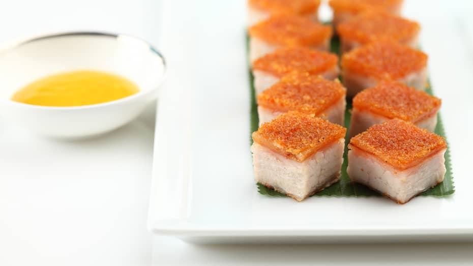 White plate with cubes of Barbecued Pork Belly with crispy skin, white bowl with dipping sauce